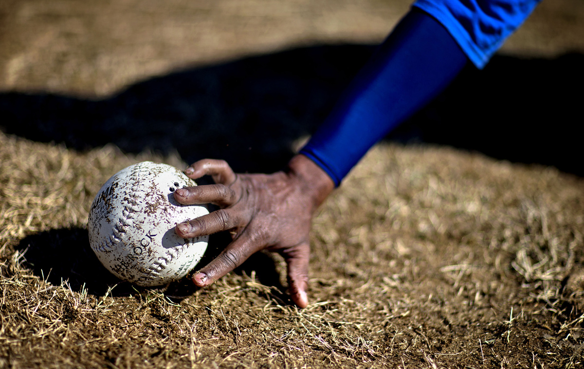 Jimmie Burnette, who lost his vision to a brain tumor in 2010, reaches for the ball which beeps during a blind baseball worko