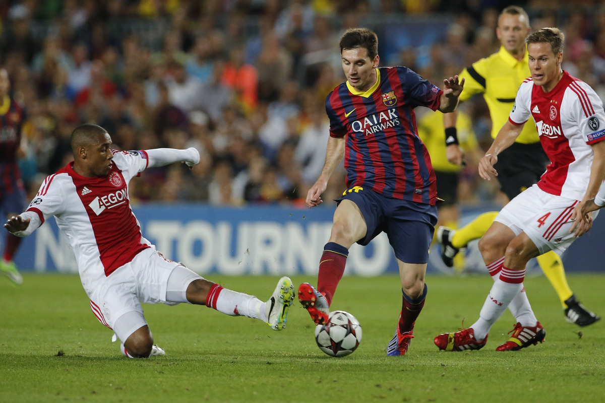 Ajax players Stefano Denswil, left, and Ajax's Christian Poulsen, right, try and stop Barcelona's Lionel Messi, center, durin
