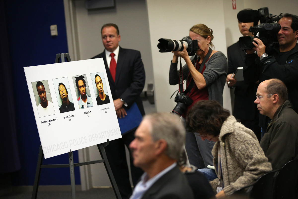 Pictures of the suspects charged in last Thursday's mass shooting at Cornell Square Park are put on display during a press co