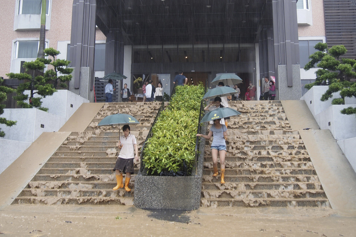 Guests walk down steps at the Hoya Hot Springs Resort & Spa inundated with flood waters from Typhoon Usagi in Chihpen, Taitun