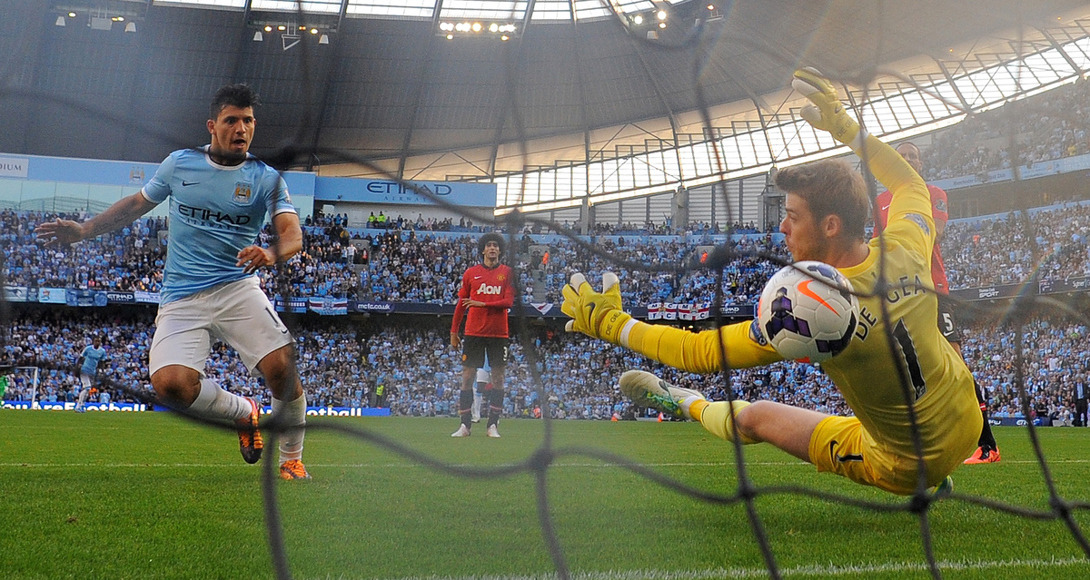 Manchester City's Argentinian forward Sergio Aguero (L) scores his teams third goal past Manchester United's Spanish goalkeep