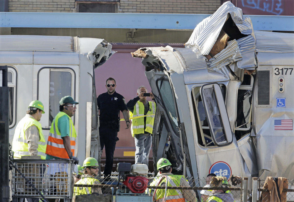Authorities inspect the wreckage of two Chicago Transit Authority trains that crashed Monday, Sept. 30, 2013, in Forest Park,