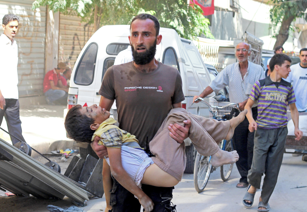 A man carries the body of a child allegedly killed by a pro-government forces sniper in the northern Syrian city of Aleppo on