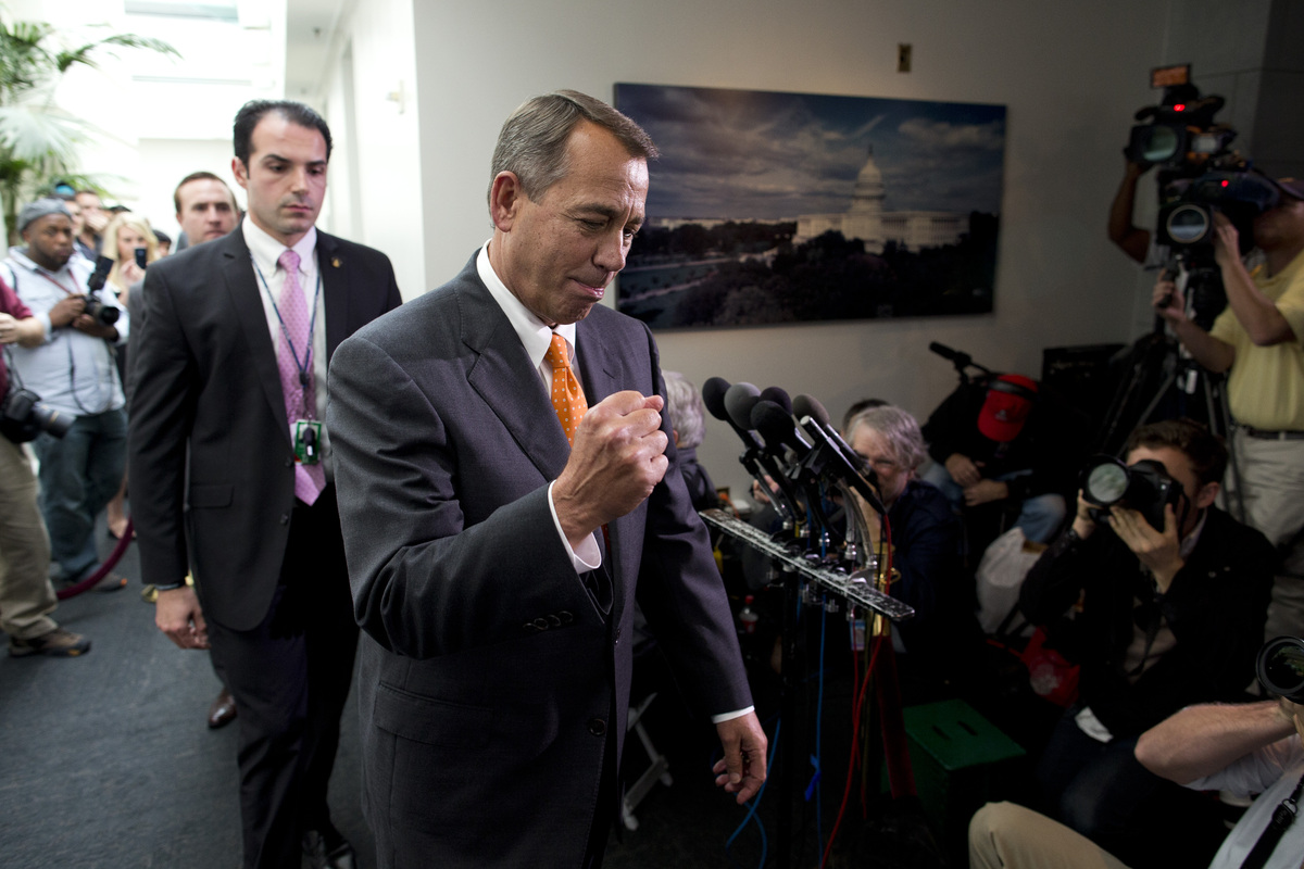 Speaker of the House Rep. John Boehner, R-Ohio, pumps his fist as he walks past reporters after a meeting with House Republic