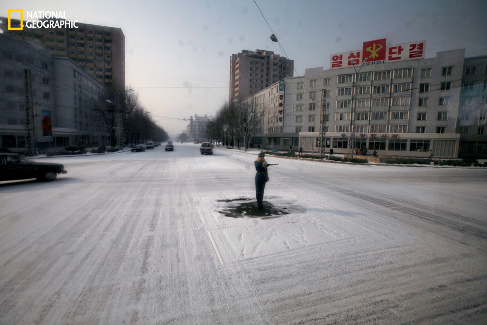 A traffic guard goes through the motions in the capital of Pyongyang, where streets are almost empty of cars. (David Guttenfe