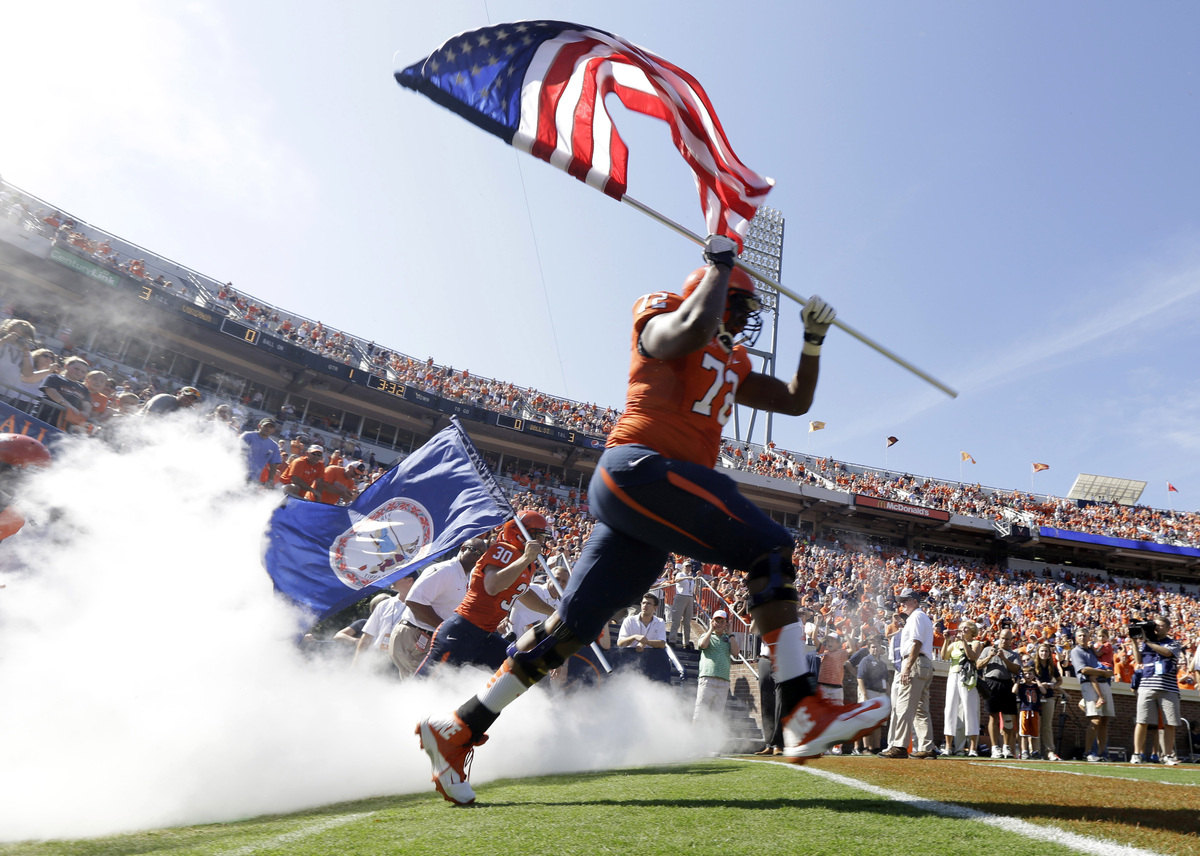 Virginia offensive tackle Eric Smith (72) carries the Amaerican flag onto the field for an NCAA college football game against