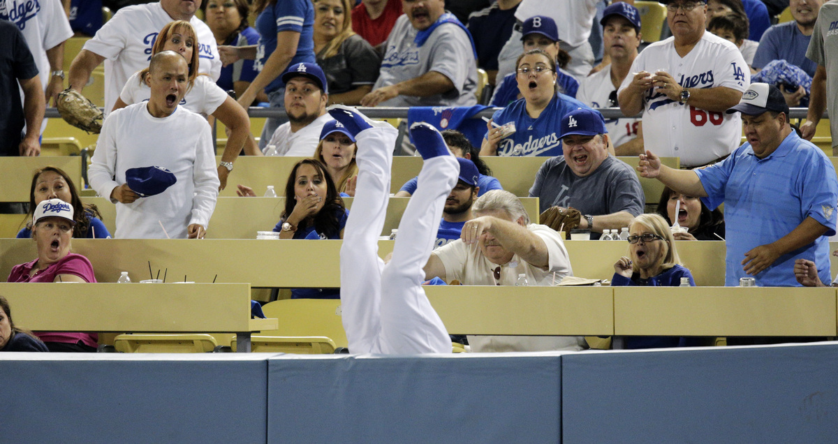Fans react as Los Angeles Dodgers left fielder Carl Crawford falls upside down over the rail after catching a foul ball hit b