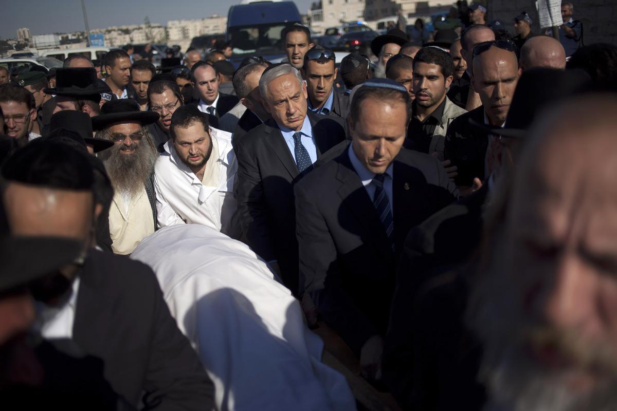 Israeli Prime Minister Benjamin Netanyahu, center, escorts the body of Rabbi Ovadia Yosef during his the funeral in Jerusalem