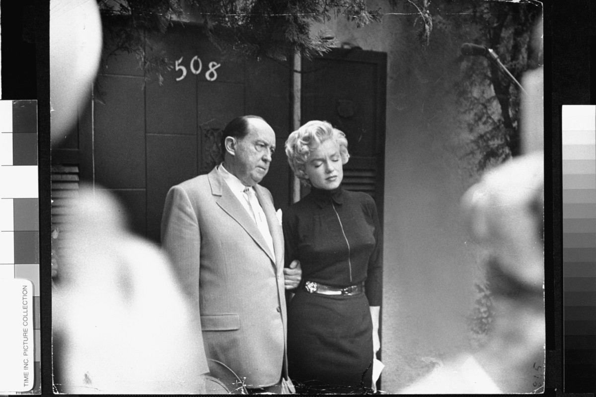 Tearful actress Marilyn Monroe w. her lawyer Jerry Giesler clutching her arm as she comes out in front of home to face dozens