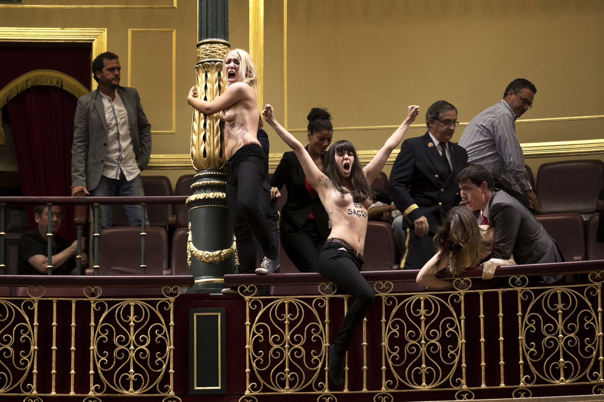 Activists from the women's movement Femen protest and are dragged away by security officers during a protest at the Spanish P