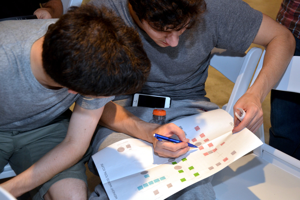 Matthew Slotkin, an employee of the hedge fund Bridgewater Associates Inc., right, checks off puzzles that his team, the Alph