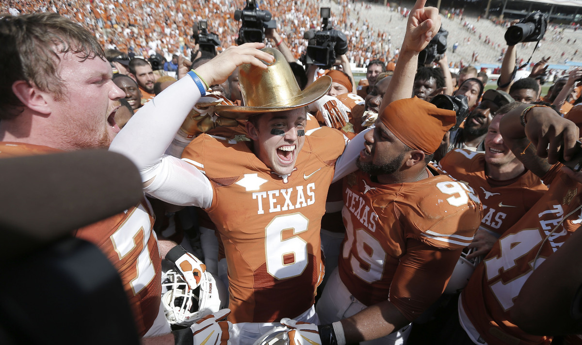 CORRECTS SPELLING OF FIRST NAME TO DESMOND, NOT DESOMOND - Texas quarterback Case McCoy (6) dons the golden hat trophy as he