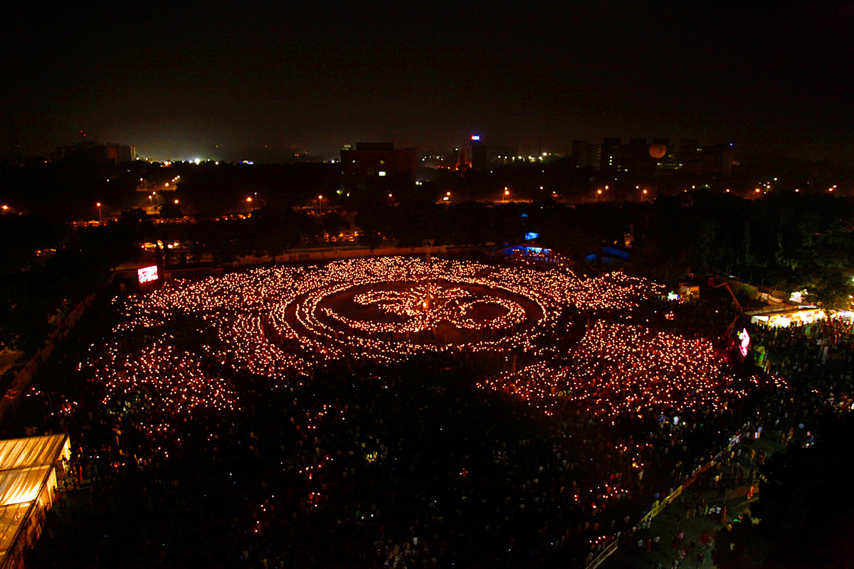 Thousands of Indian Hindu devotees light candles in the form of the 'Aum' religious symbol during a Maha Arti (Mass Prayer) o