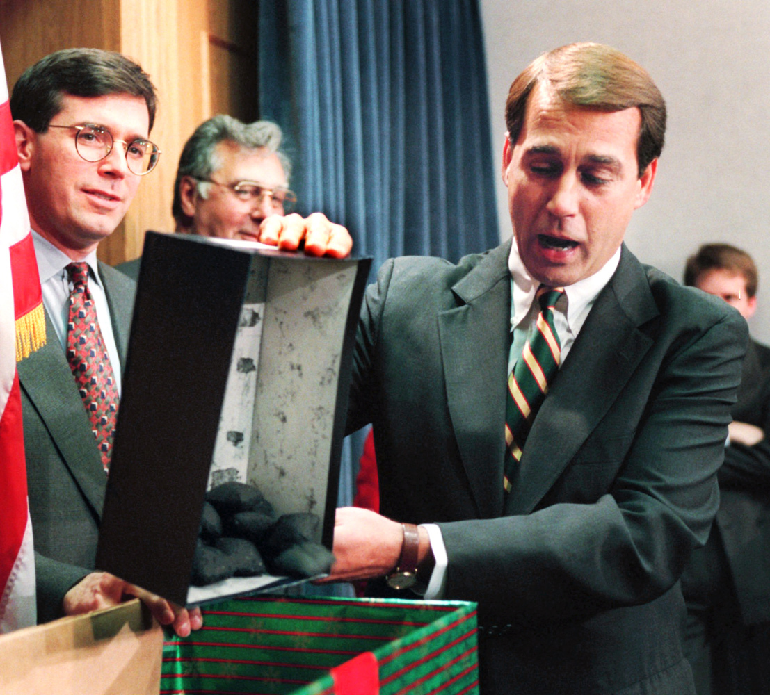In this Dec. 21, 1995, file photo Rep. John Boehner, R-Ohio, dumps out coal, his so-called Christmas gift to President Clinto