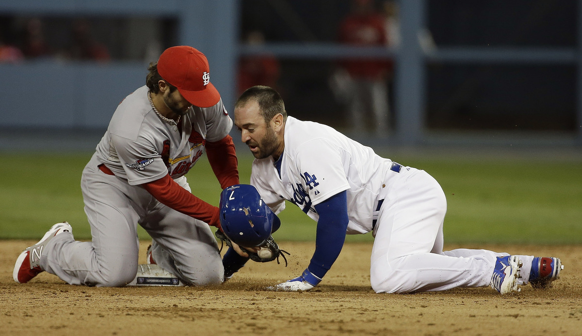 St. Louis Cardinals' Pete Kozma tags out Los Angeles Dodgers' Nick Punto as he is picked off second during the seventh inning