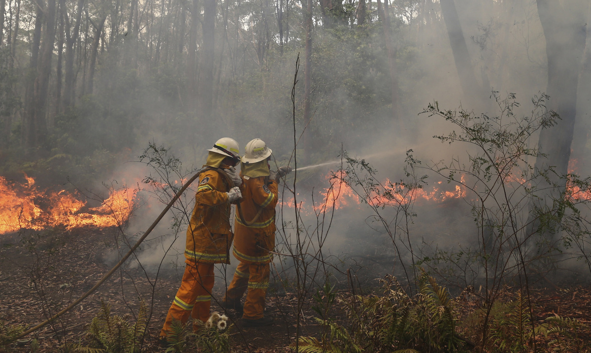 A firefighter hoses to control flames near houses at Bilpin, 75 kilometers (47 miles) west of Sydney, Australia, Tuesday, Oct