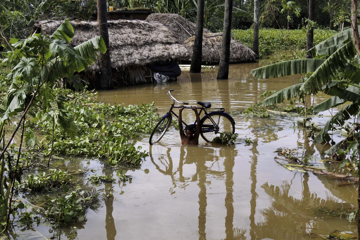 An Indian man carries his bicycle after water levels rose following heavy rainfall in Jajpur district, 120 kilometers (75 mil
