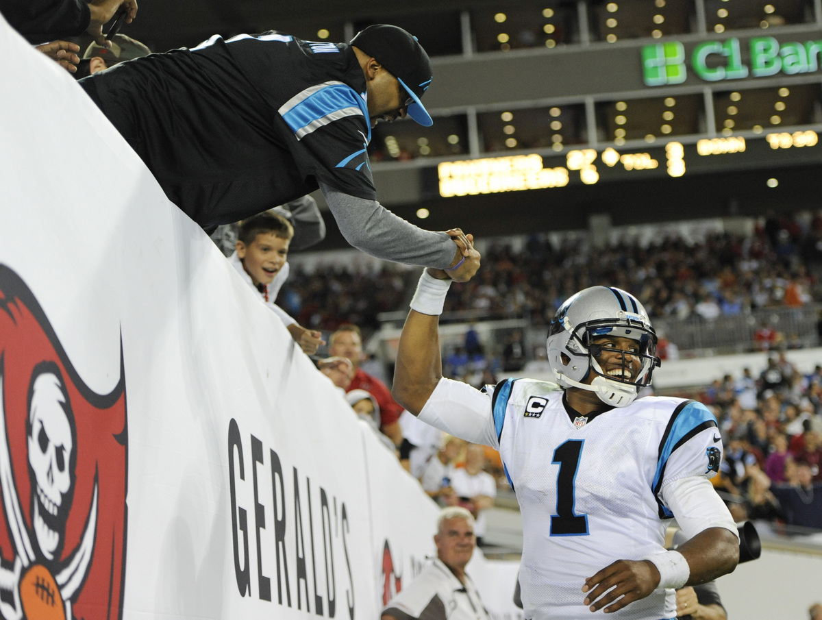 Carolina Panthers quarterback Cam Newton (1) shakes hands with a fan after Panthers fullback Mike Tolbert scored a touchdown