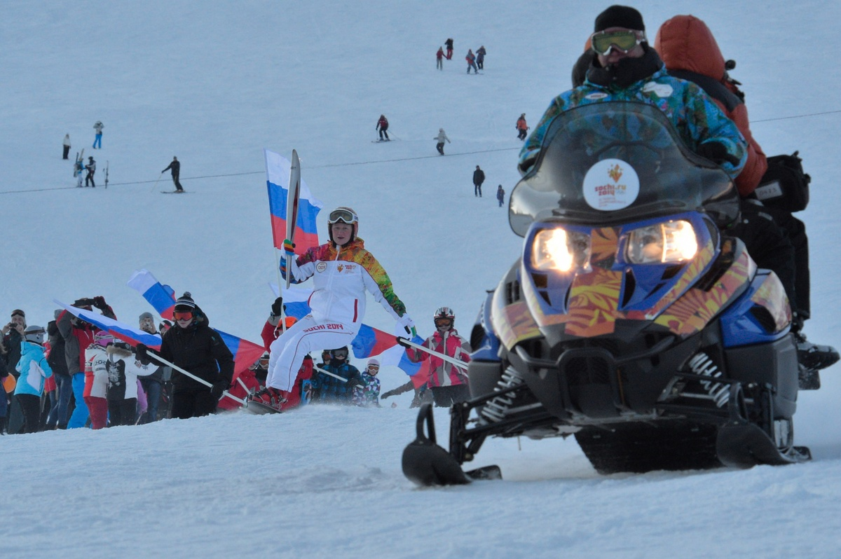 Torch bearer Olga Nasonova holding an Olympic torch snowboards in the Sheregesh winter sports resort in Tashtagol, Kemerovo r