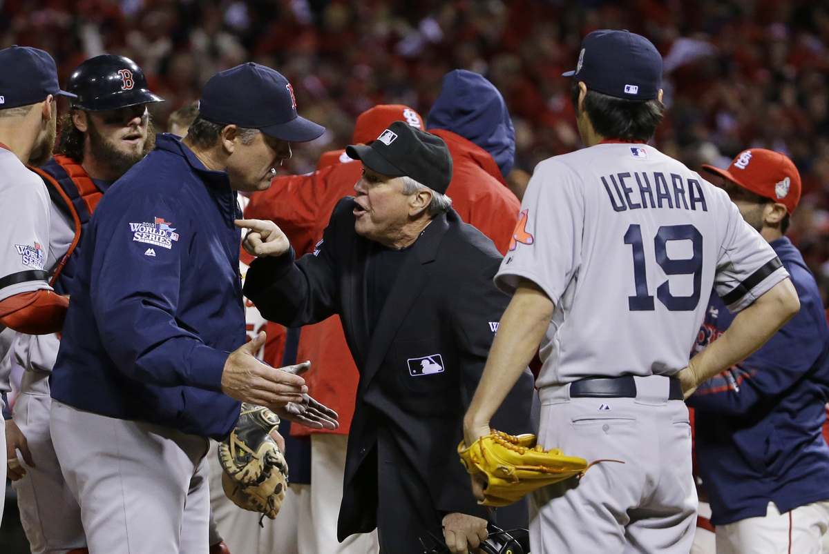 Boston Red Sox manager John Farrell argues with home plate umpire Dana DeMuth after St. Louis Cardinals scored the winning ru