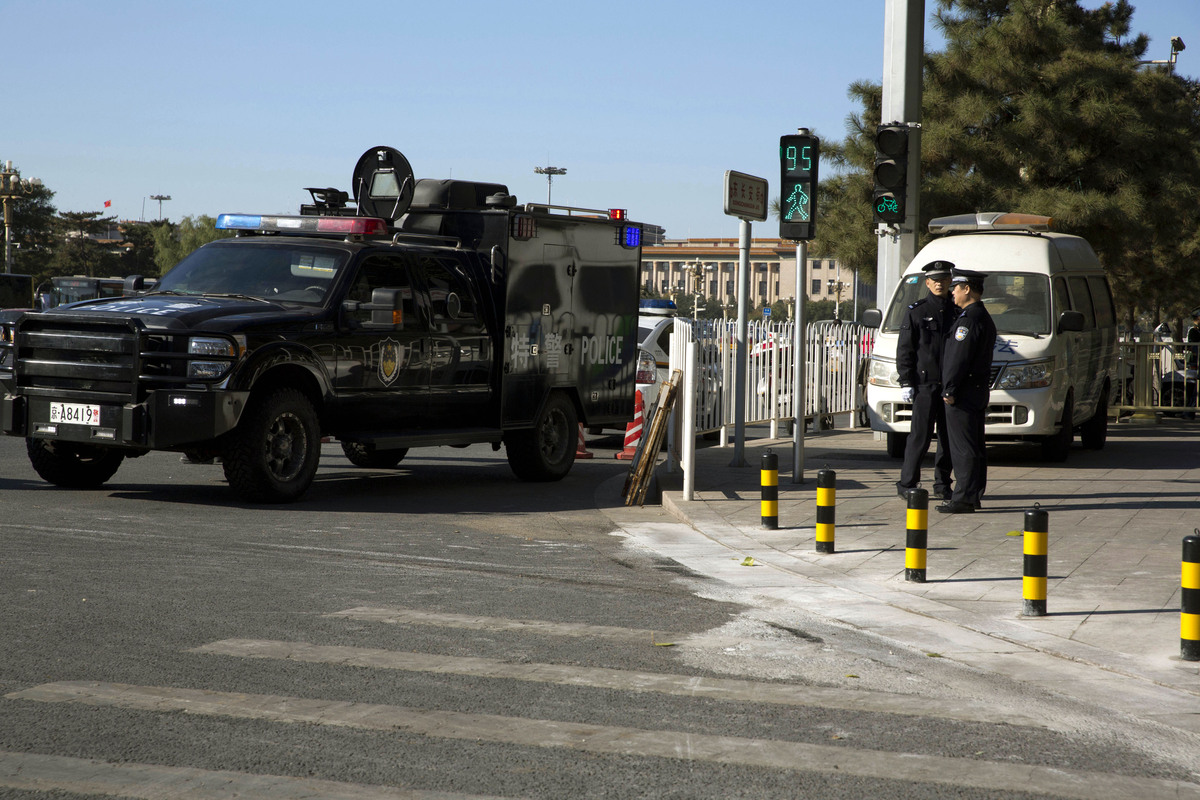 A vehicle from the Chinese police special tactical unit guards the sidewalk where it is believed a car drove up before it plo