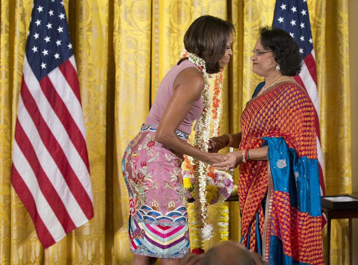 First lady Michelle Obama is offered a garland of jasmine flowers by Mythili Lee Bachu, temple chair of the Sri Siva Vishnu t