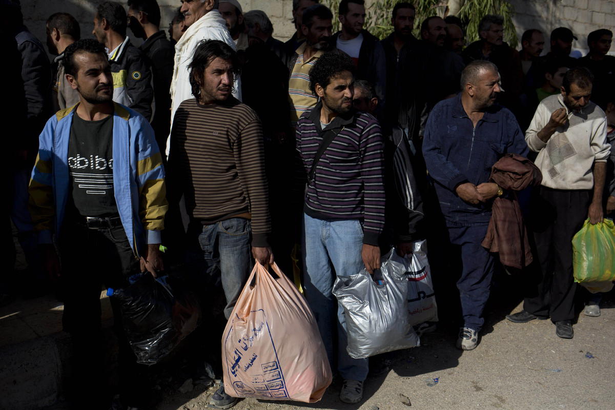 Men wait to be searched by the Syrian military after they have crossed from the rebel held suburb of Moadamiyeh to the govern