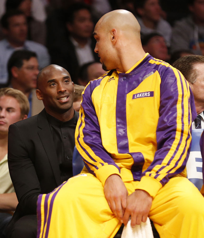 Los Angeles Lakers' Kobe Bryant, left, talks with Lakers' center Robert Sacre, right, as he sits behind the team's bench agai