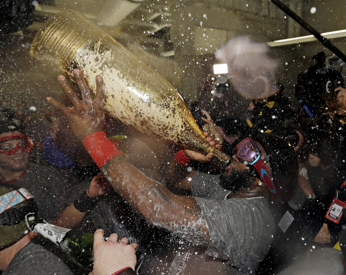 Boston Red Sox's David Ortiz drinks out of a giant bottle of Champagne as he celebrates with teammates after Game 6 of baseba