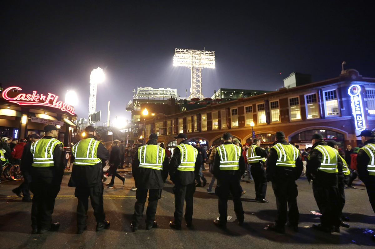 Law enforcement officials form a line along a street outside Fenway Park, background, following Game 6 of baseball's World Se