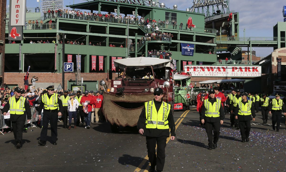 Police flank duck boats carrying Boston Red Sox players away from Fenway Park during a rolling parade in celebration of the b