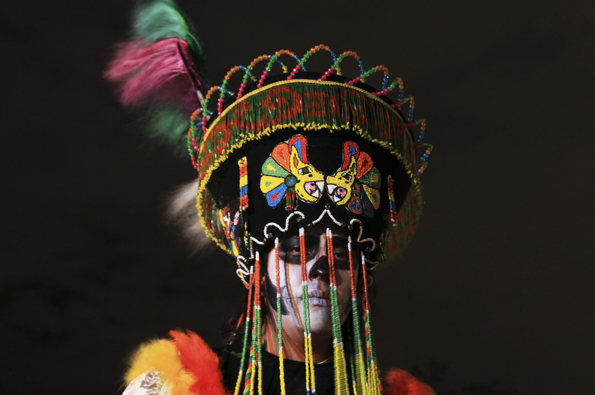 In this Wednesday, Oct. 30, 2013 photo, artist Luis Castillo poses for a photo in a costume he designed and says is a represe