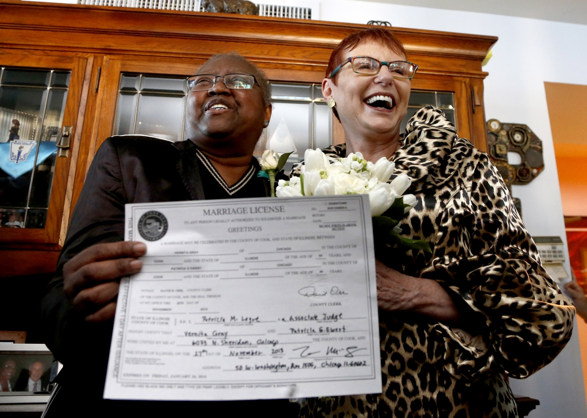 Holding their Illinois marriage license, Vernita Gray, left, and Patricia Ewert smile at friends after they were married by C