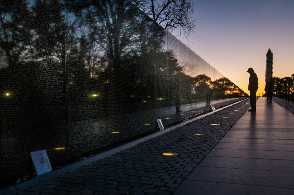A visitor at the Vietnam War Memorial in Washington passes early in the morning on Veterans Day, Monday, Nov. 11, 2013, to lo