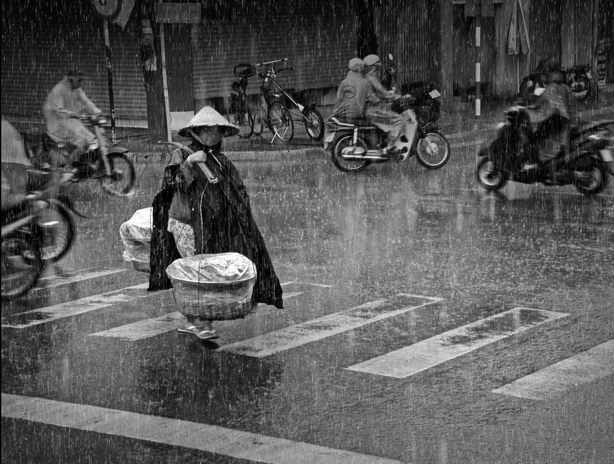 Vietnam. A woman transports potatoes to a local market. Her earnings help feed two children and her husband. On a sunny day,