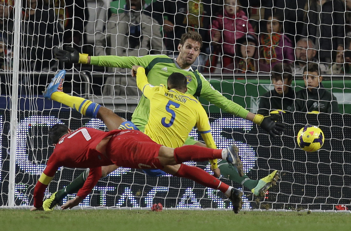 Portugal's Cristiano Ronaldo, left, scores the opening goal past Sweden goalkeeper Andreas Isaksson, background right, during