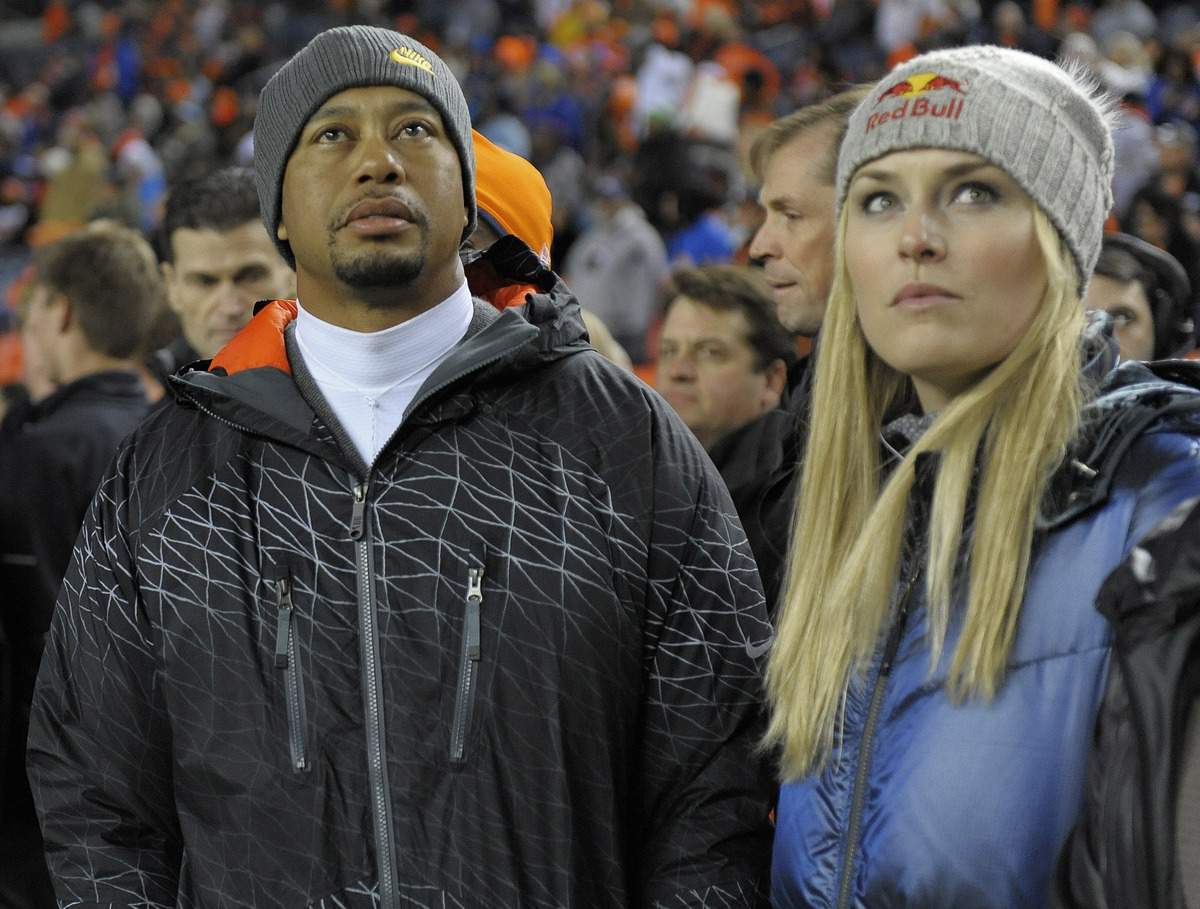 Tiger Woods, left, and Lindsey Vonn watch from the sidelines as the Denver Broncos and the Kansas City Chiefs warm up before