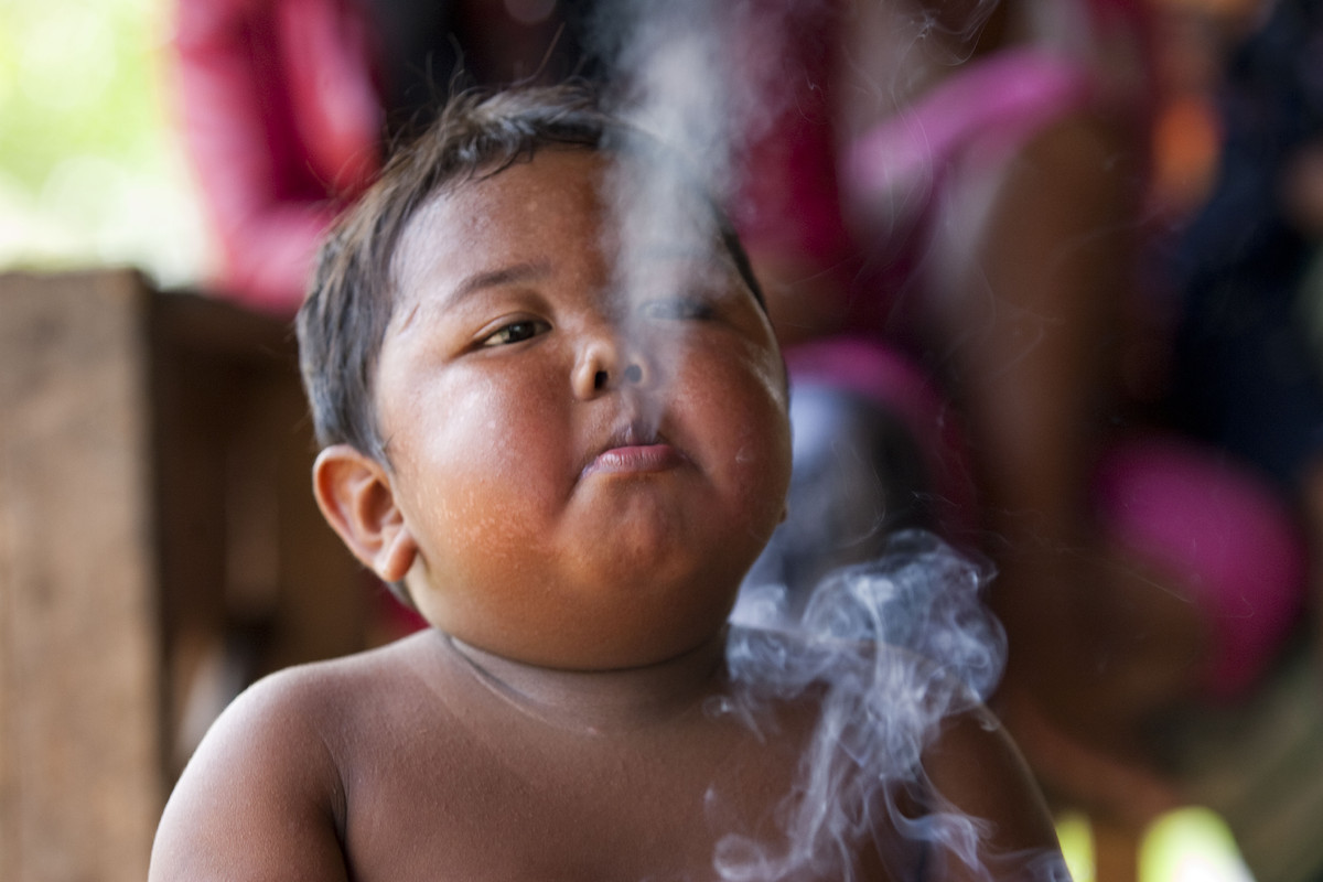 Ardi Rizal (2 years-old) smoking a cigarette while playing at the family home on May 23, 2010 in Sekayu district, South Sumat