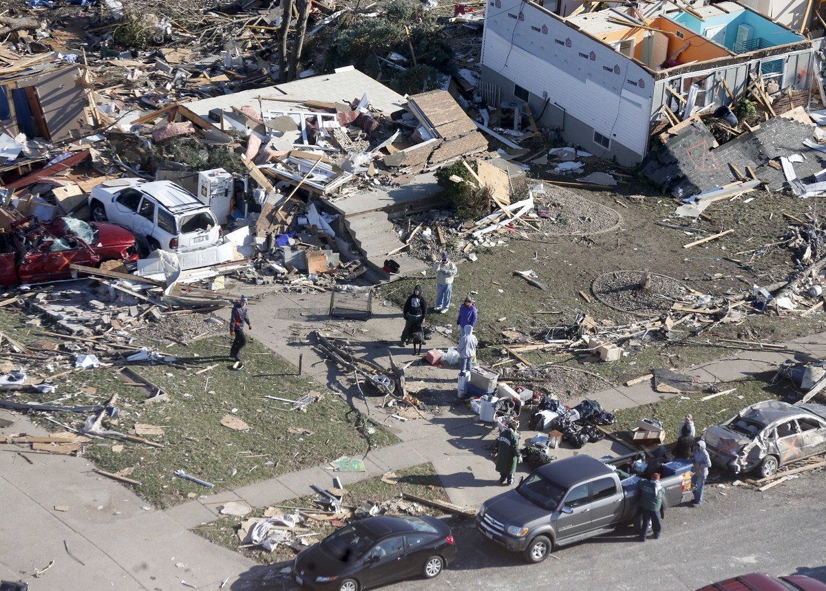 In this aerial view on Monday, Nov. 18, 2013, people look through the debris of a home that was destroyed by a tornado that h