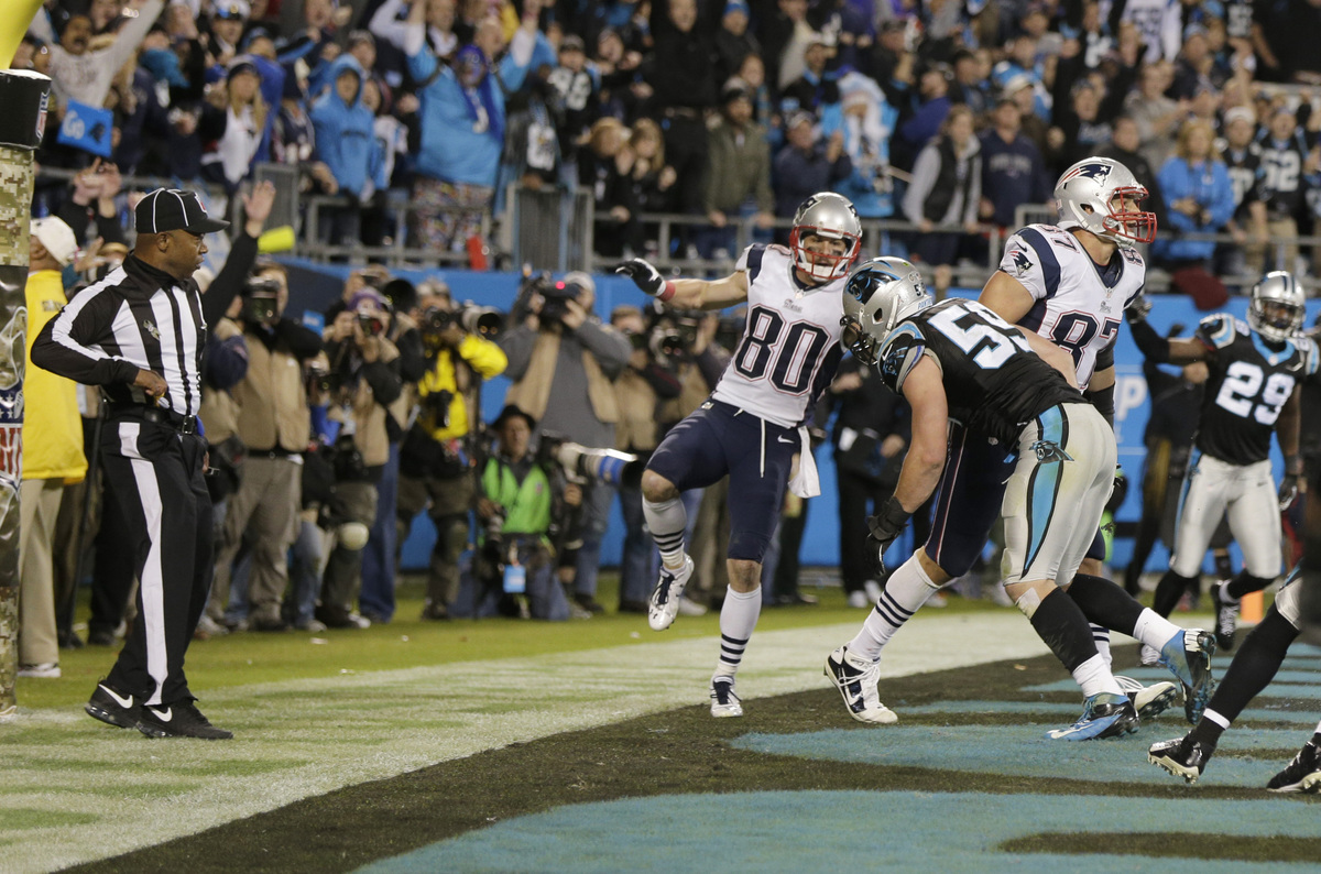 An official, left, reaches for his flag as Carolina Panthers' Luke Kuechly (59) hits New England Patriots' Rob Gronkowski (87