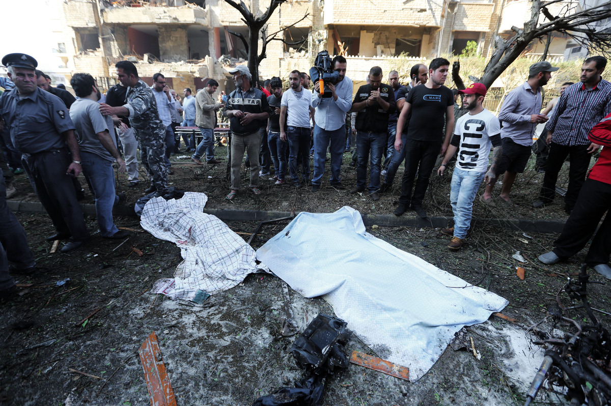 Lebanese people, gather around two dead bodies at the scene where two explosions have struck near the Iranian Embassy killing
