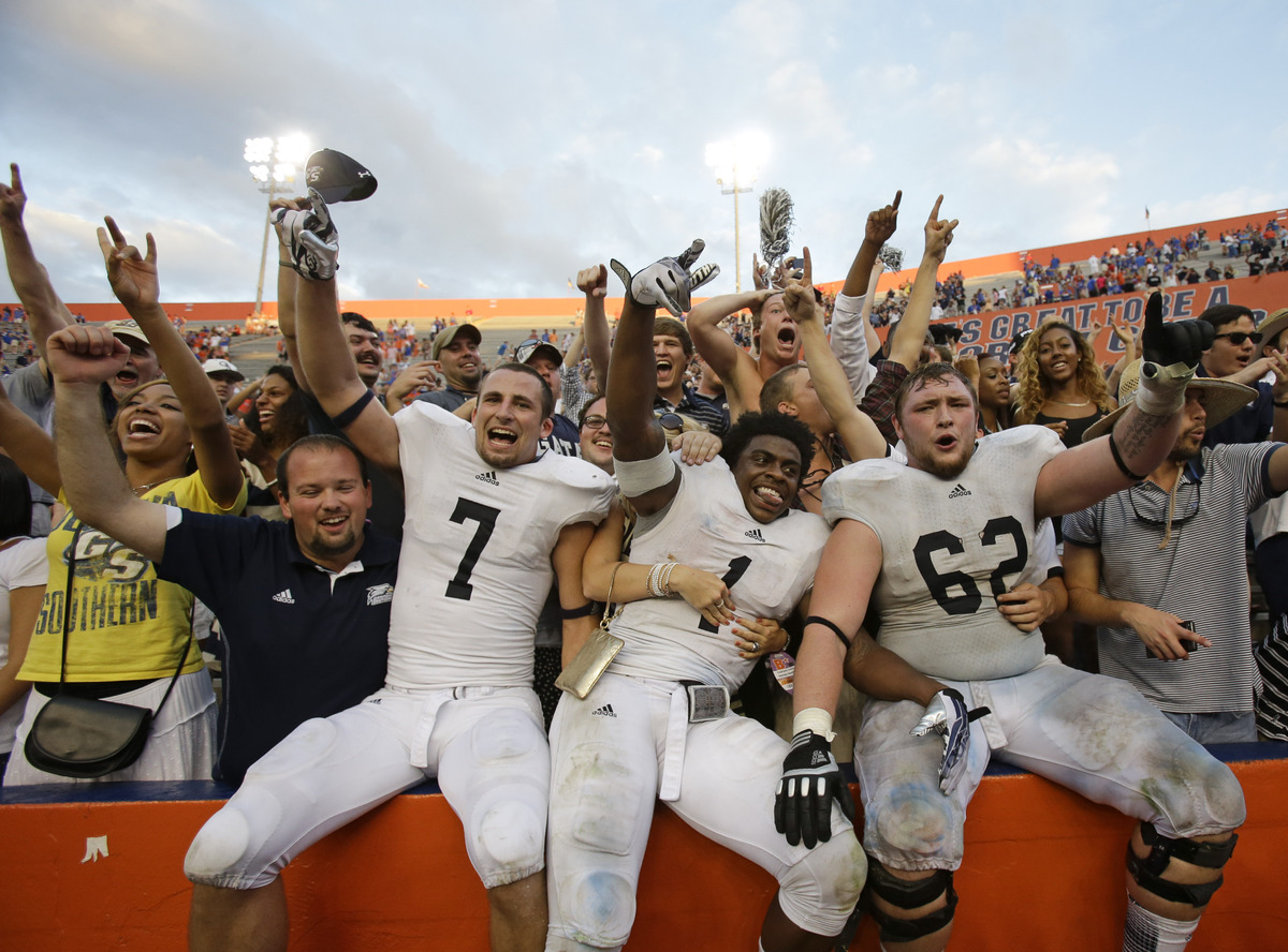 Georgia Southern players Matt Dobson (7), Jerick McKinnon (1) and Zach Lonas (62) celebrate a 26-20 victory over Florida with