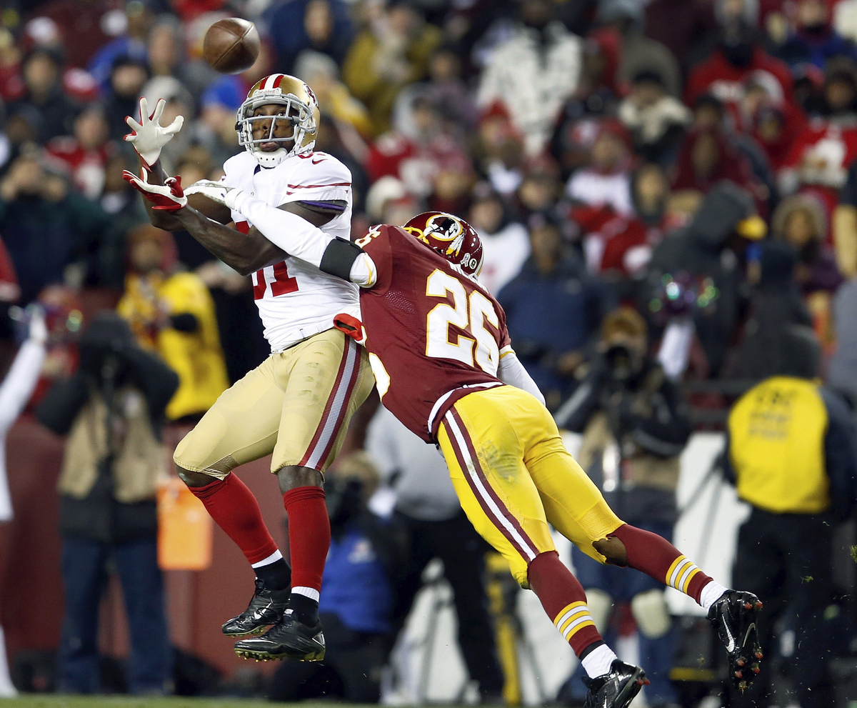 San Francisco 49ers wide receiver Anquan Boldin pulls in a pass under pressure from Washington Redskins cornerback Josh Wilso