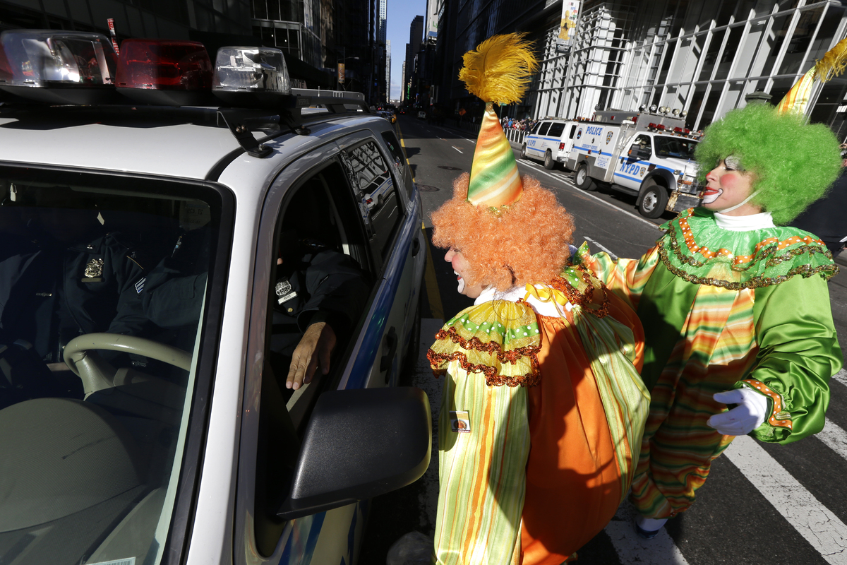 Women dressed as clowns talk to a police officer during the Macy's Thanksgiving Day Parade, Thursday, Nov. 28, 2013, in New Y