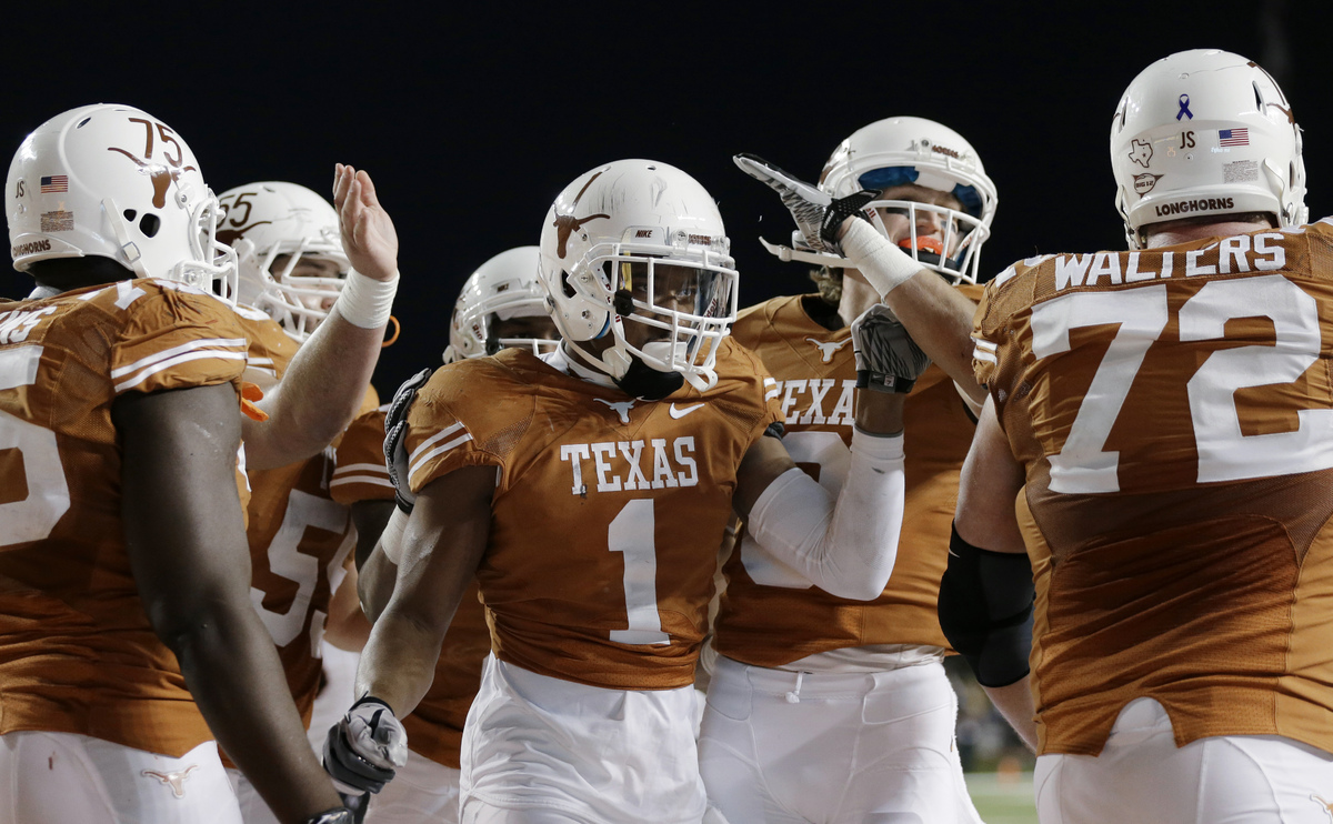 Texas' Mike Davis (1) is congratulated by teammates after he scored a touchdown against Texas Tech during the second half of