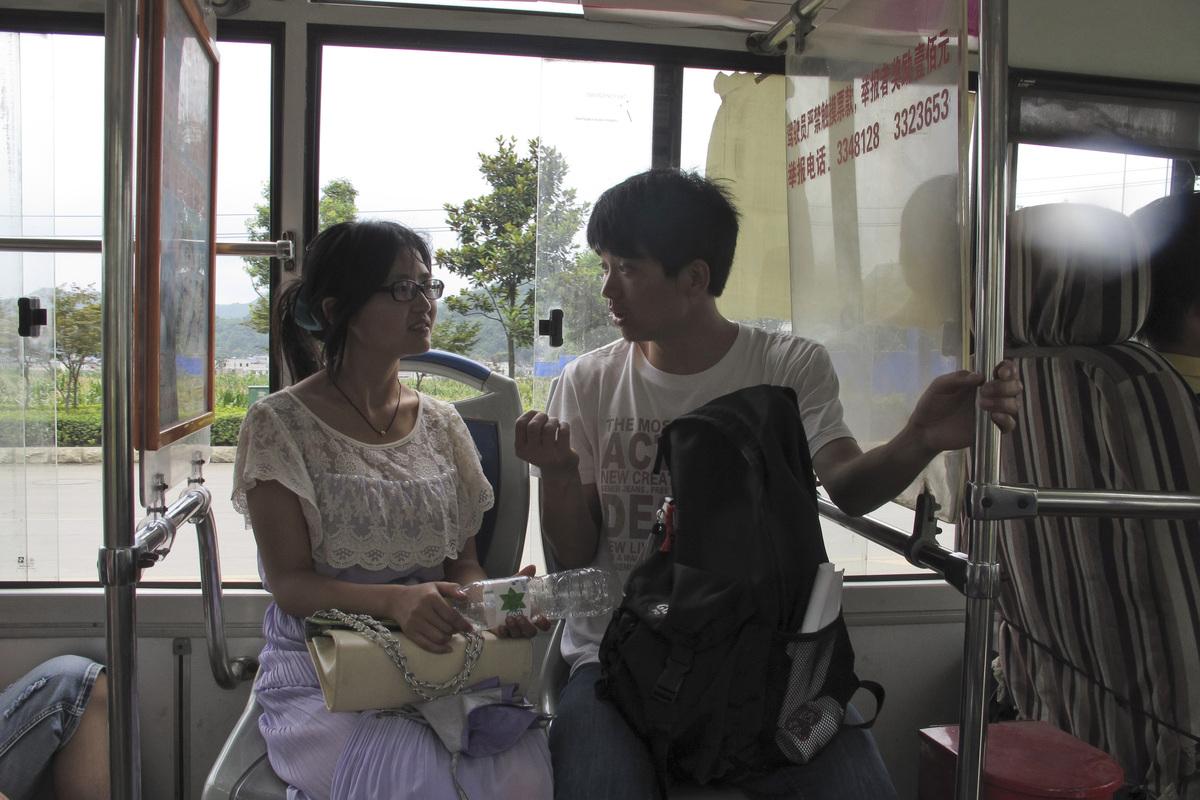 In this photo taken Tuesday, July 16, 2013, Mu Zhengwu, right, sits on a city bus with his girlfriend, Cheng Yanzi, in Anshun