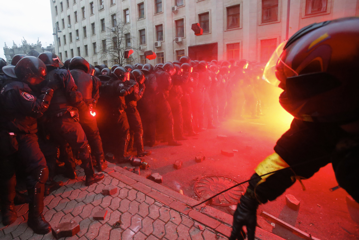 Protesters throw stones as they clash with police outside the presidential administration building in downtown Kiev, Ukraine,