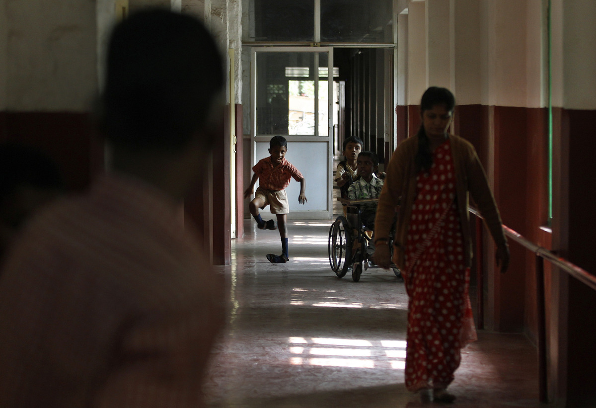 A boy runs down the corridor to go to his classroom at the Association of People with Disability run school on International