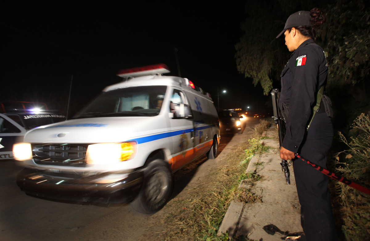 A police agent stands guard as an ambulance leaves the village of Hueypoxtla, Mexico, Wednesday, Dec. 4, 2013. (AP Photo/Marc