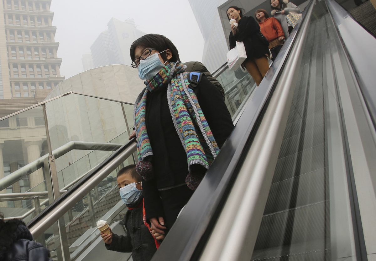 A woman and a child wear the masks to protect them from air pollution in Shanghai, China, Friday, Dec. 6, 2013. (AP Photo/Eug